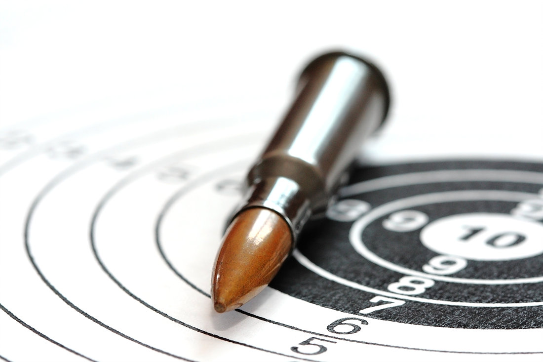 single rifle bullet on paper target for shooting practice
